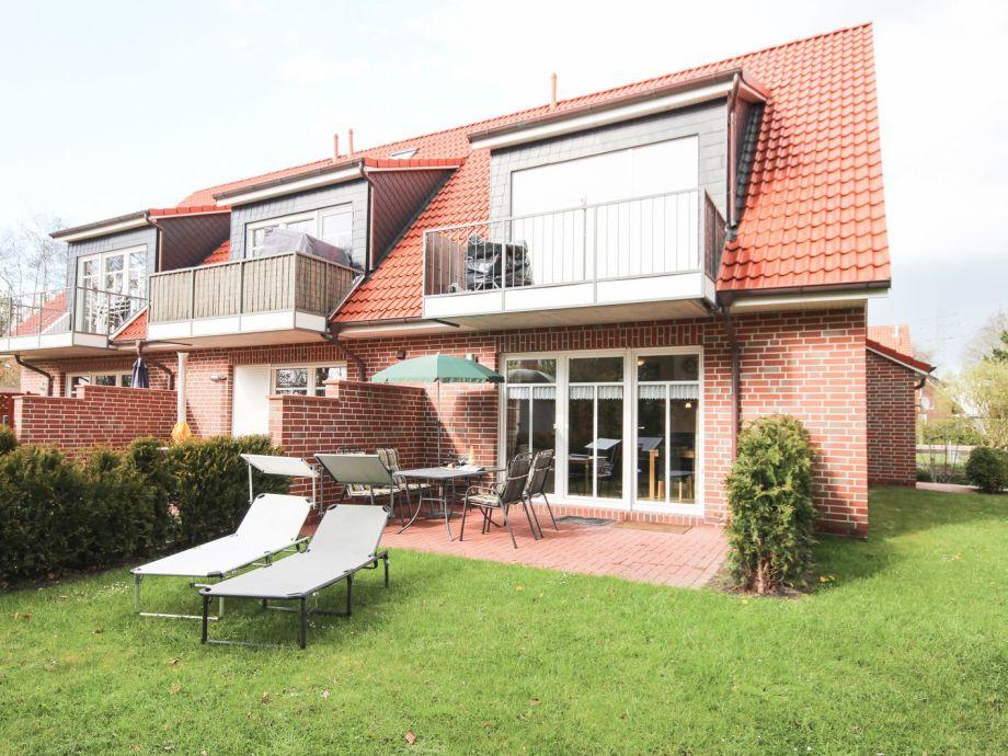 Garten mit Liegestühlen und möblierter Terrasse