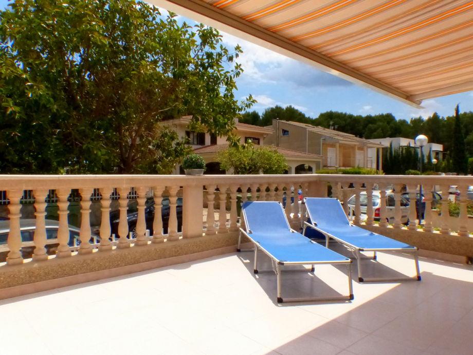 schöne Terrasse mit Sonnenliegen und Markiese