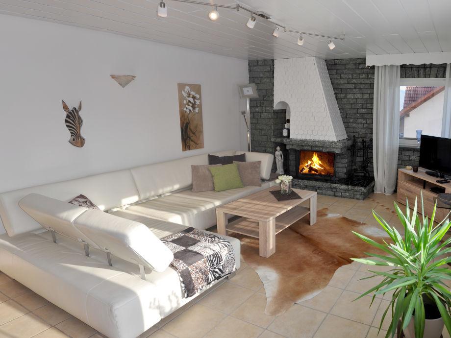 Wohnzimmer mit offenem Kamin und SAT-TV