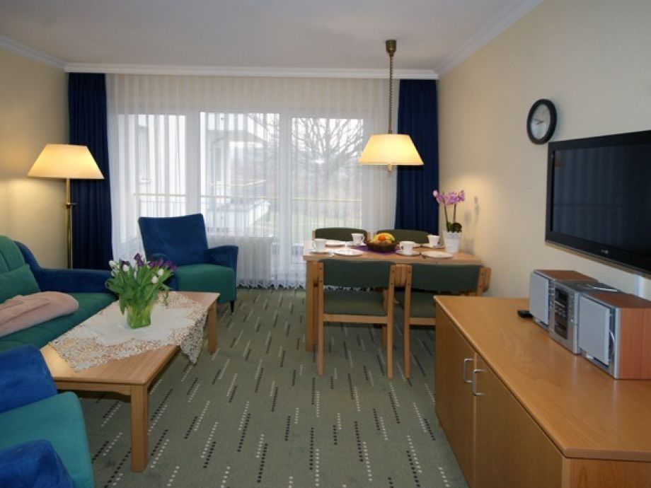 Wohnzimmer mit TV-Gerät und Essplatz