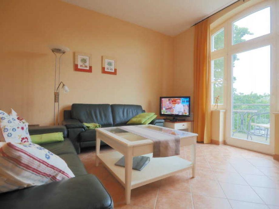 Wohnbereich mit Flachbildfernseher und Zugang zum Balkon