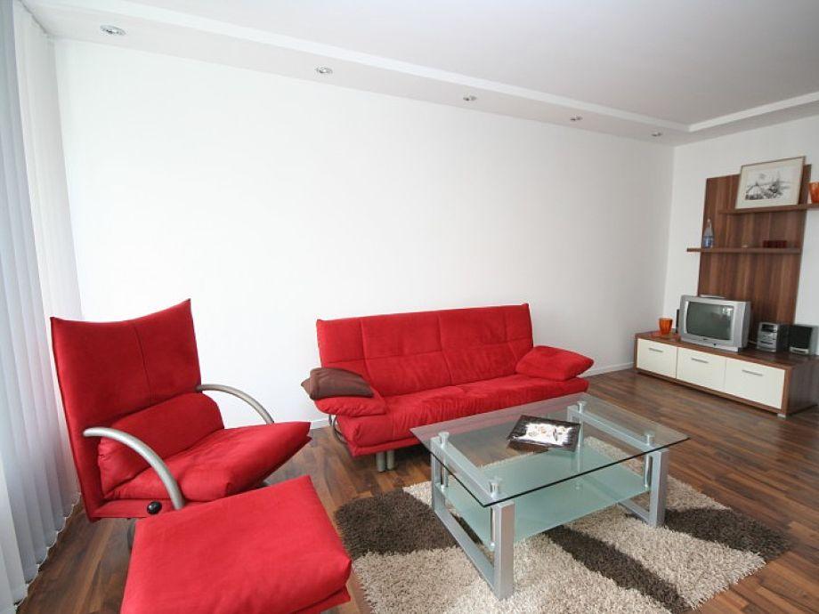 Wohnzimmer mit Sofa, Flach-TV, Essecke und Doppelbett.
