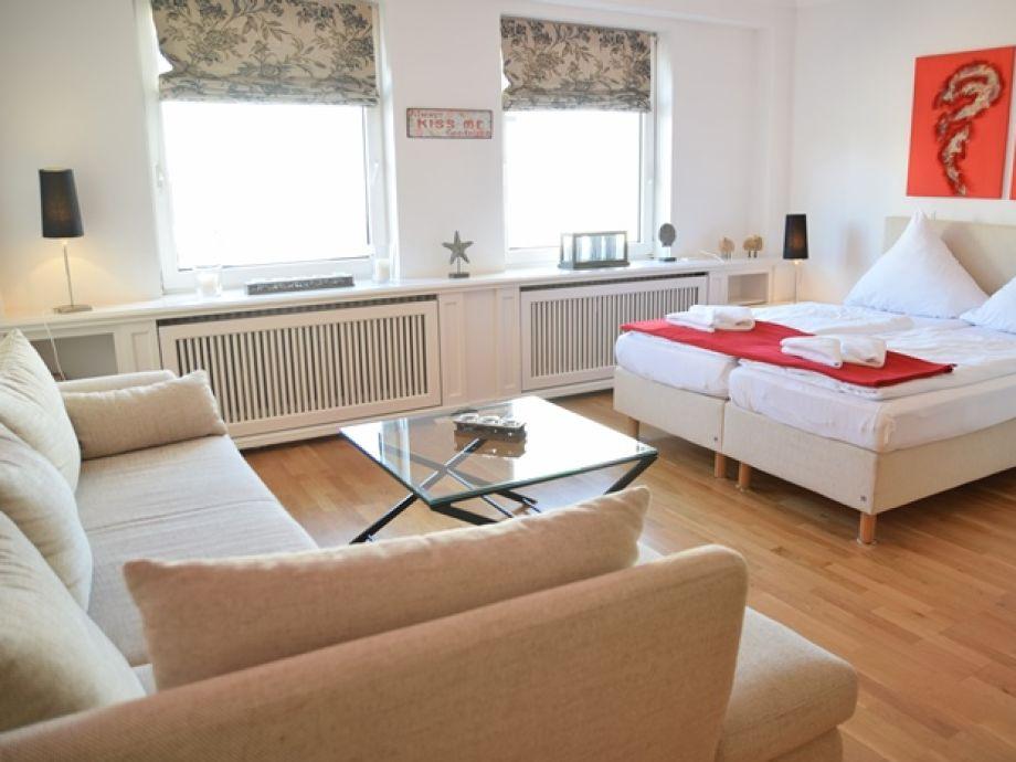 Freundliches, helles Wohnzimmer mit Schlafbereich