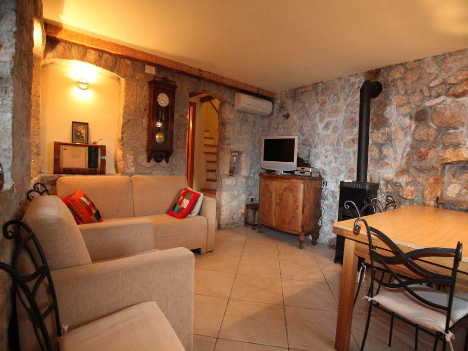 Wohnküche mit einer Natursteinwand und Kamin