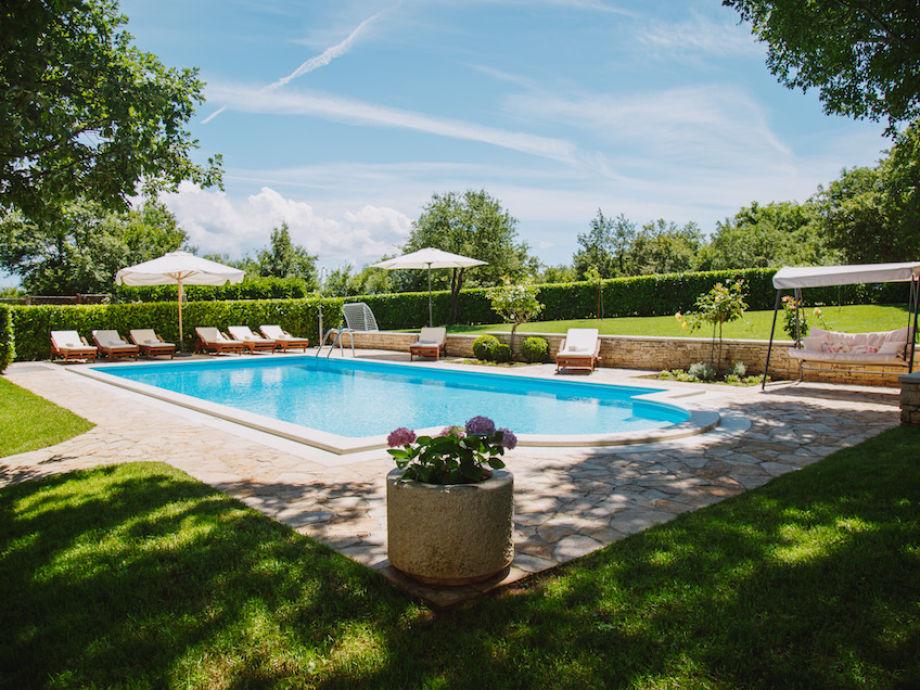 Der Pool ist von einem üppigen Garten umgeben