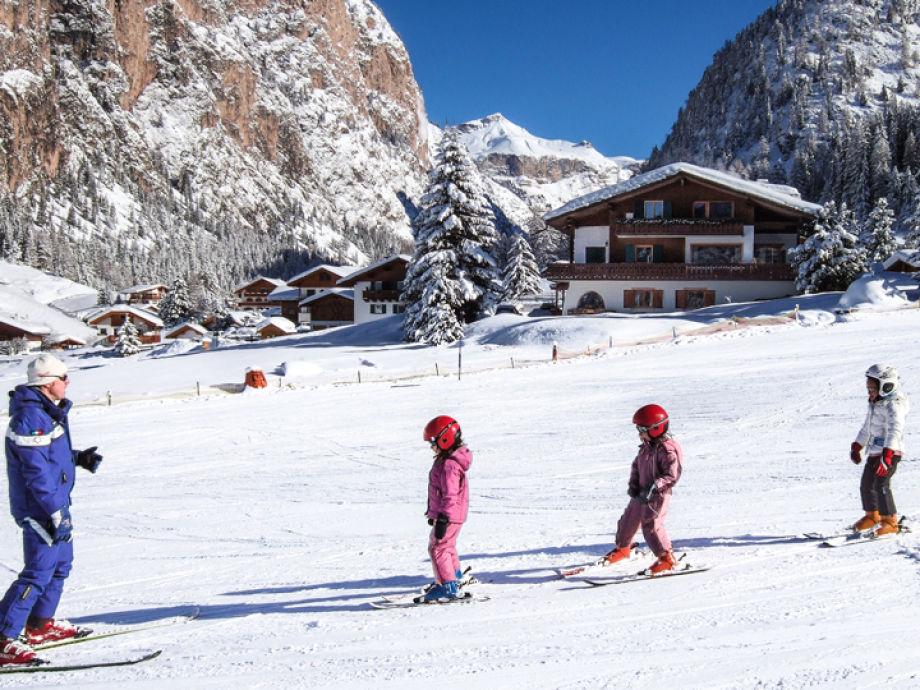 Skiunterricht auf der Piste vor dem Haus