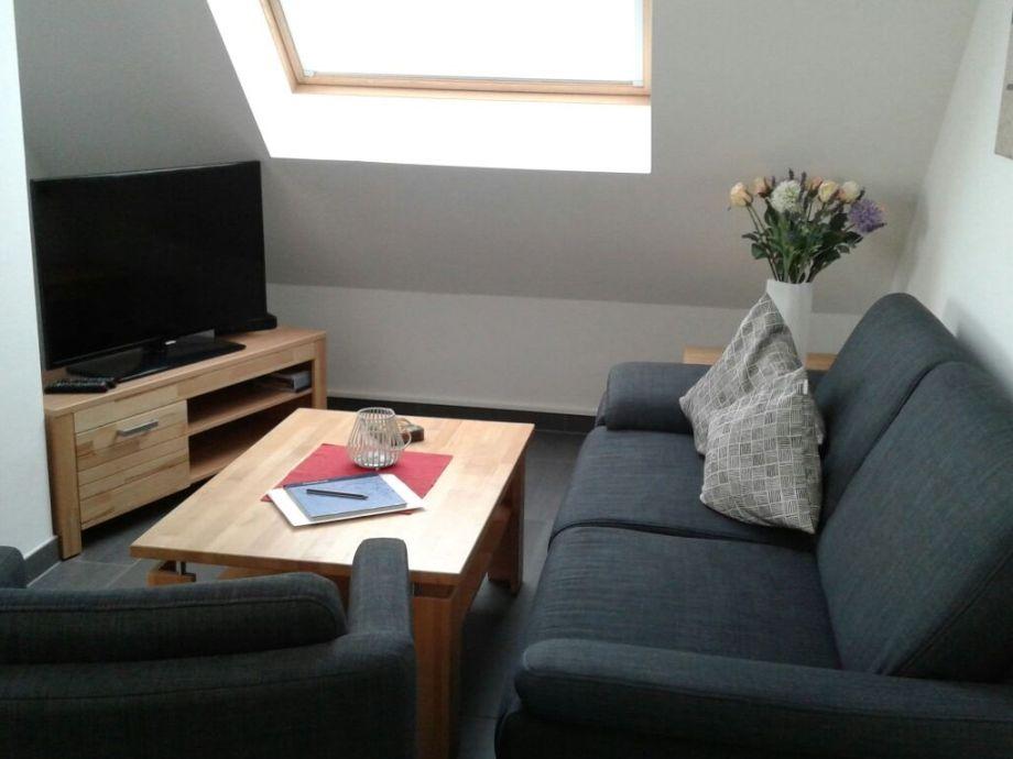 Im Wohnzimmer befindet sich ein Sofa und ein Sessel.