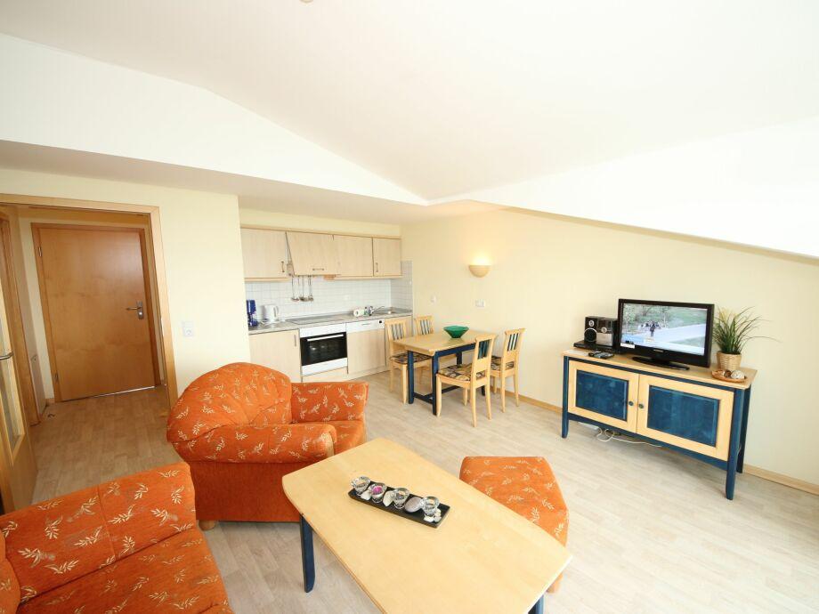 Wohnzimmer mit TV und offener Küche