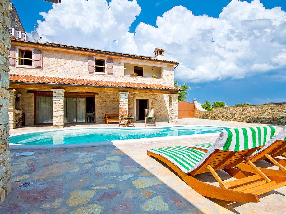 Der Außenbereich mit Pool und Sonnenliegen