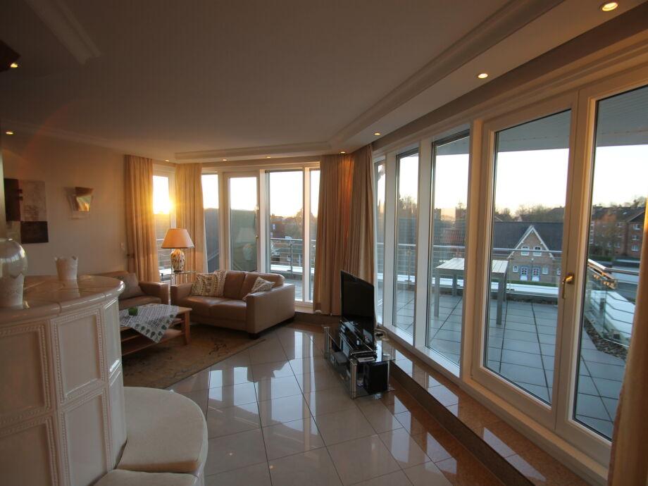 Wohnzimmer mit großen Panoramafenstern und direktem Dachterrassenzugang