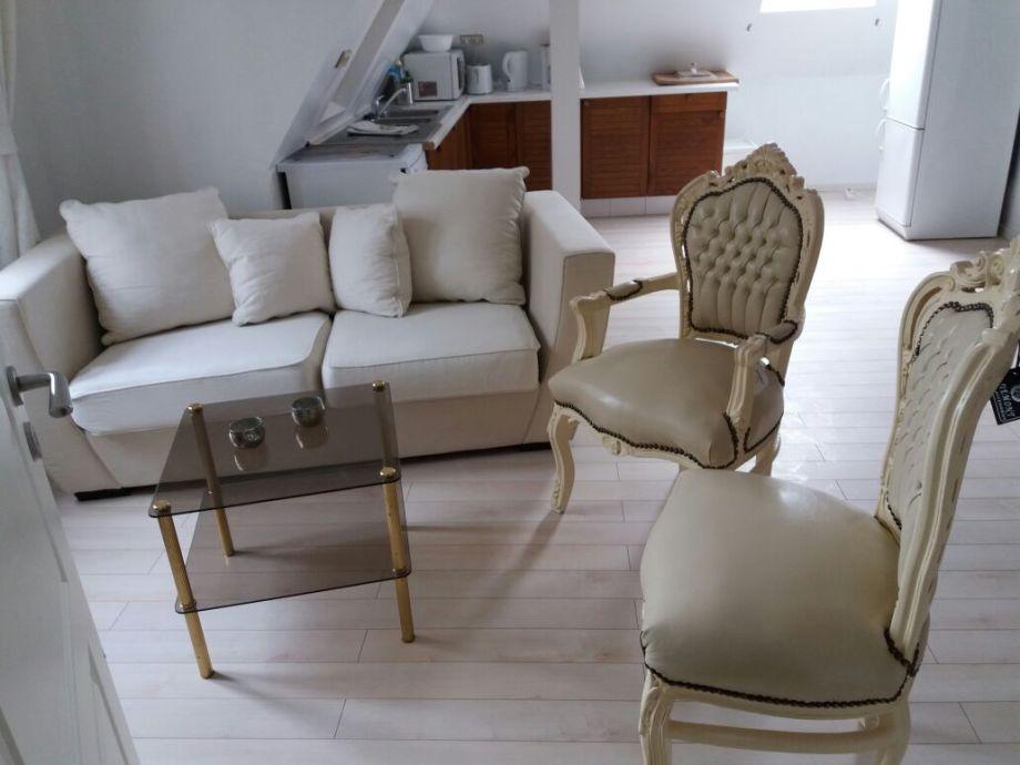 Wohnbereich mit kleinem Sofa und zwei Stühlen