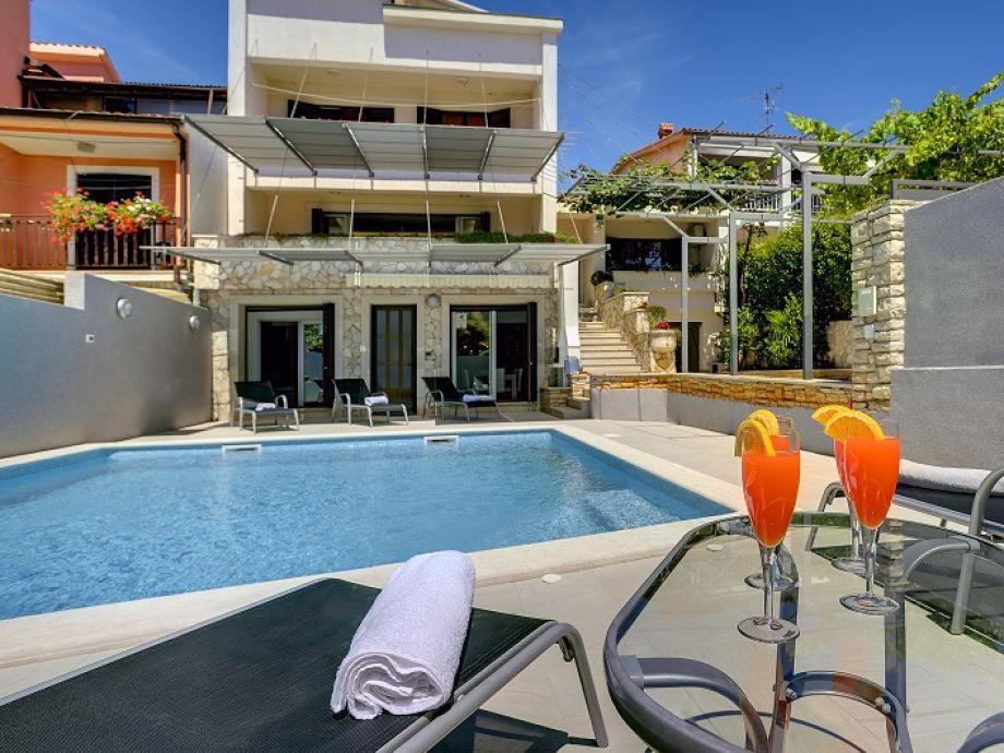 Ansicht des Ferienhauses aus dem Hof über den Pool