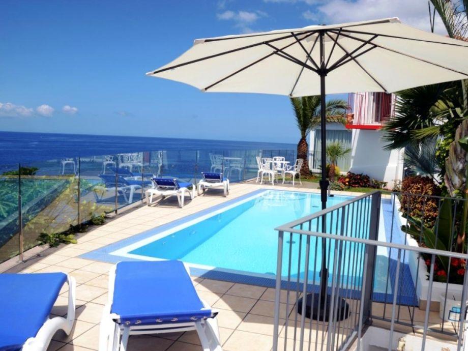 Blick über Pool zu Villa und Meer