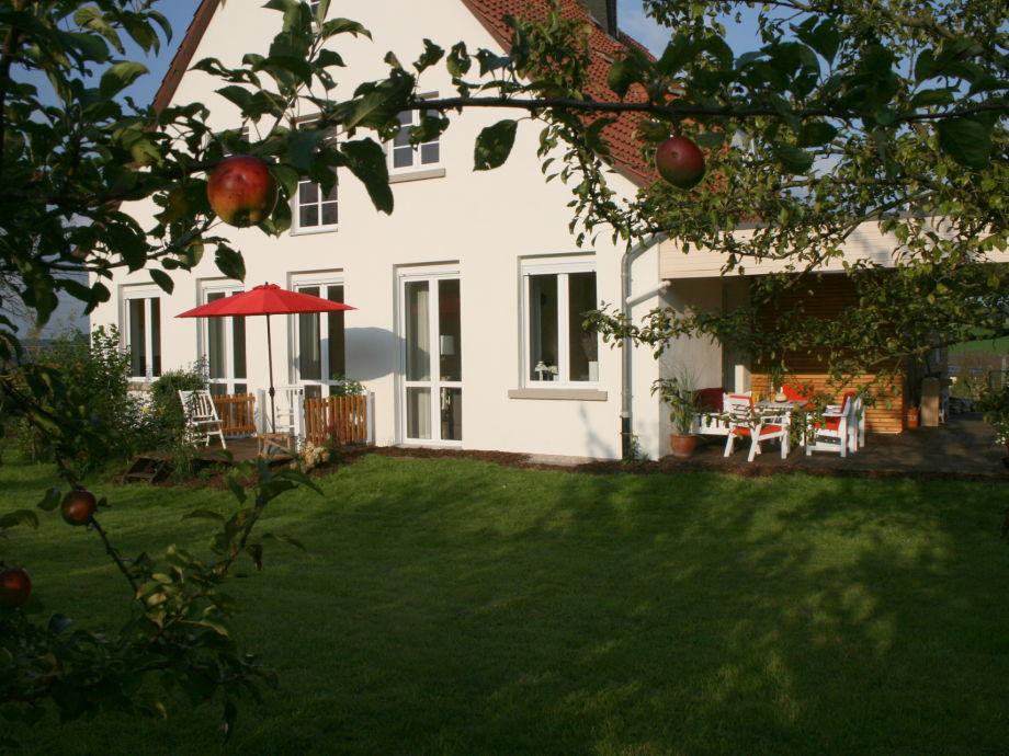Westansicht mit kleiner Terrasse und großer Veranda